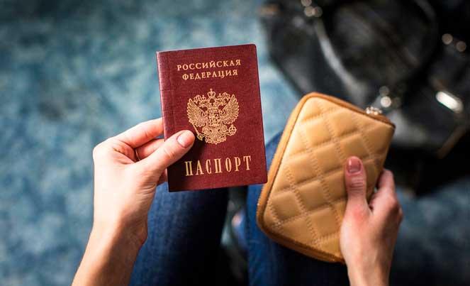 девушка держит в руках паспорт и кошелек